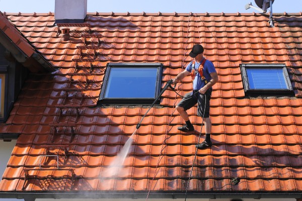 man cleaning roof with pressure washer