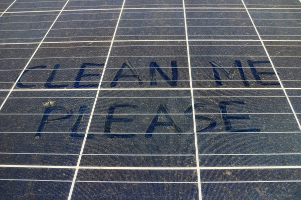 Clean Me Please writing on a dirty solar panel