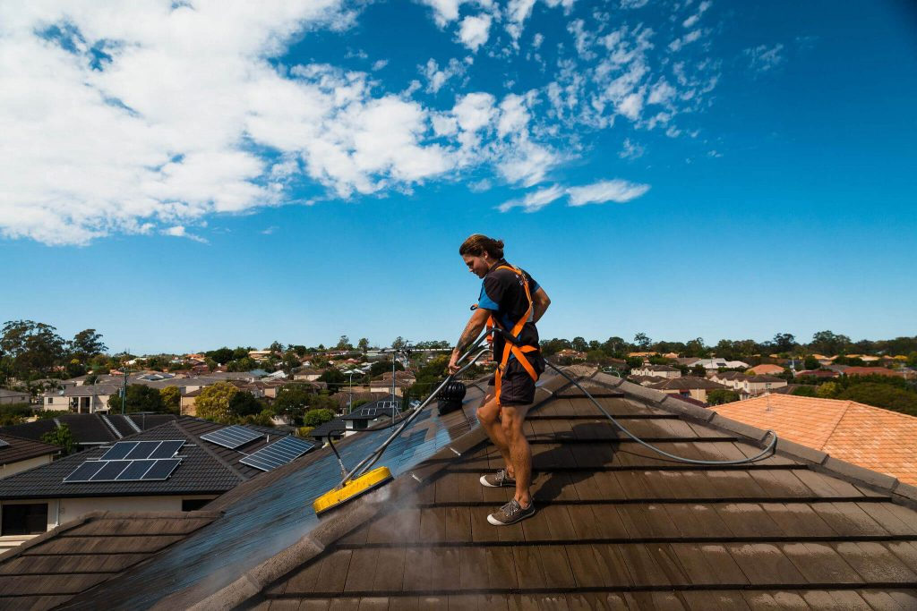 Man cleaning a house roof with bristle pressure washer